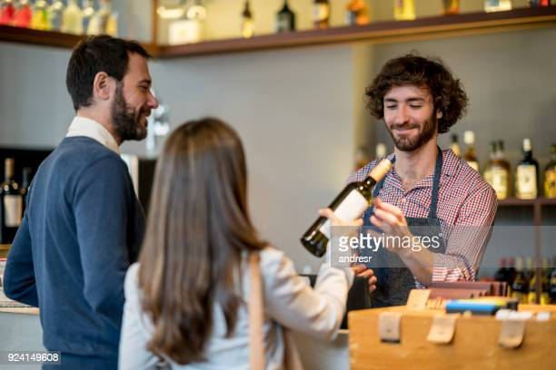 couple at a wine store checking out purchasing a bottle of white wine and friendly salesman helping them - liquor store stock pictures, royalty-free photos & images