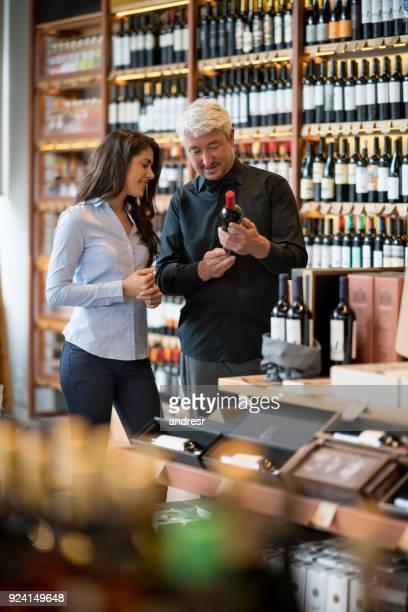 Paar in einem Weingut, Blick auf eine Flasche Rotwein kaufen