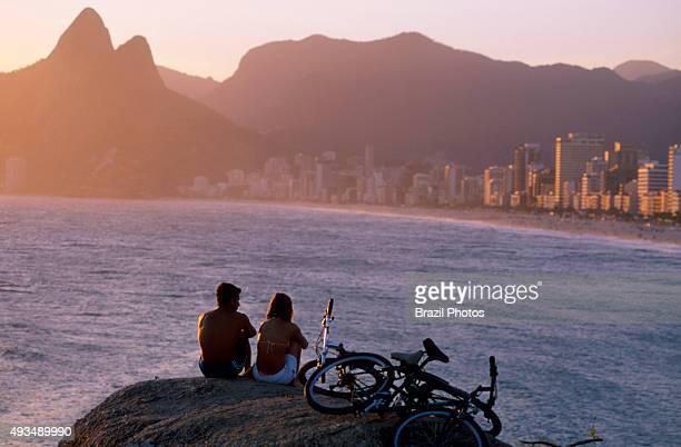 Couple at Arpoador stones enjoying the sunset at Ipanema beach Rio de Janeiro Brazil