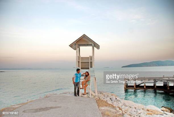 Couple At Beach Against Sky During Sunset