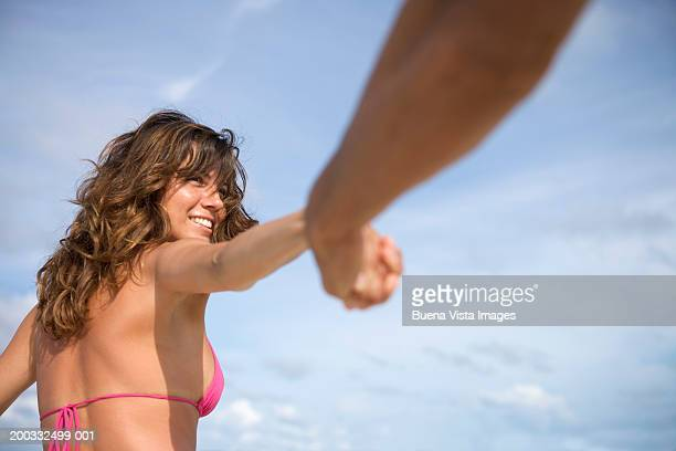 Couple at beach, woman pulling man's hand