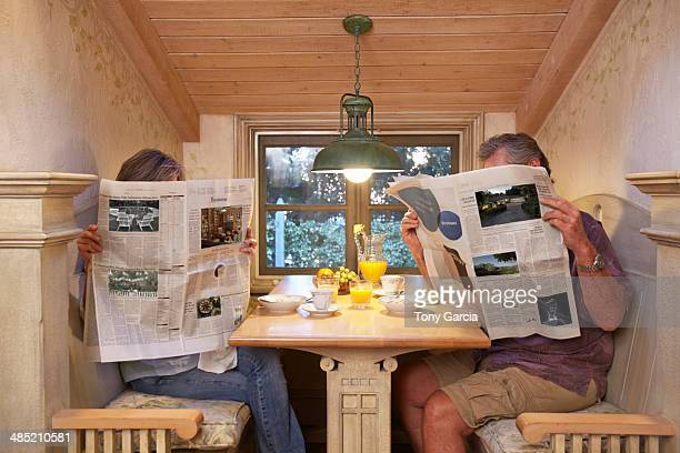 couple at breakfast table, ignoring each other, reading newspapers - viso nascosto foto e immagini stock