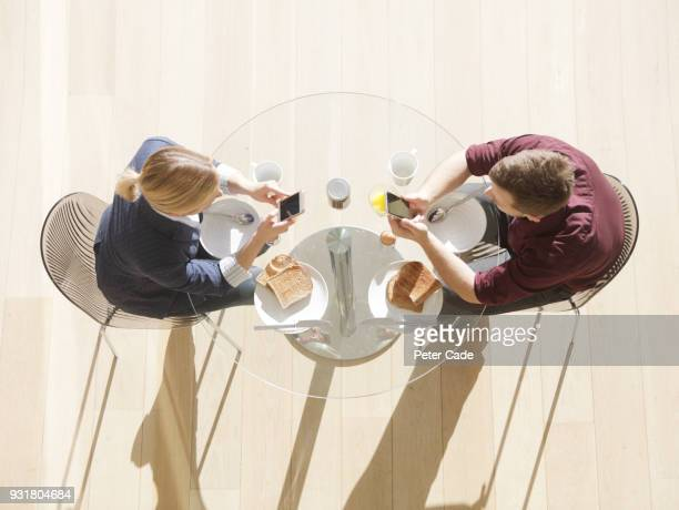 couple at breakfast table on phones, areal view - rank stock pictures, royalty-free photos & images