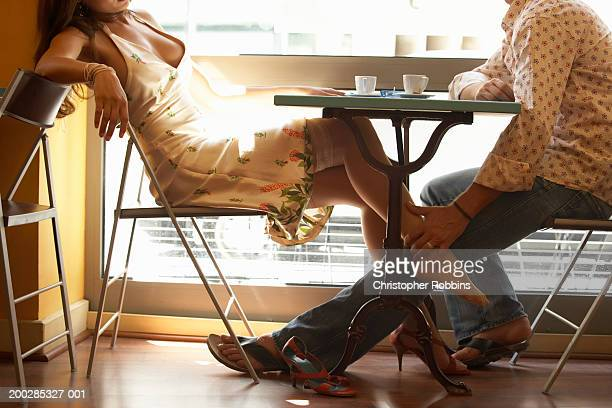 couple at cafe table, man rubbing woman's ankle beneath table - man touching womans leg stock photos and pictures