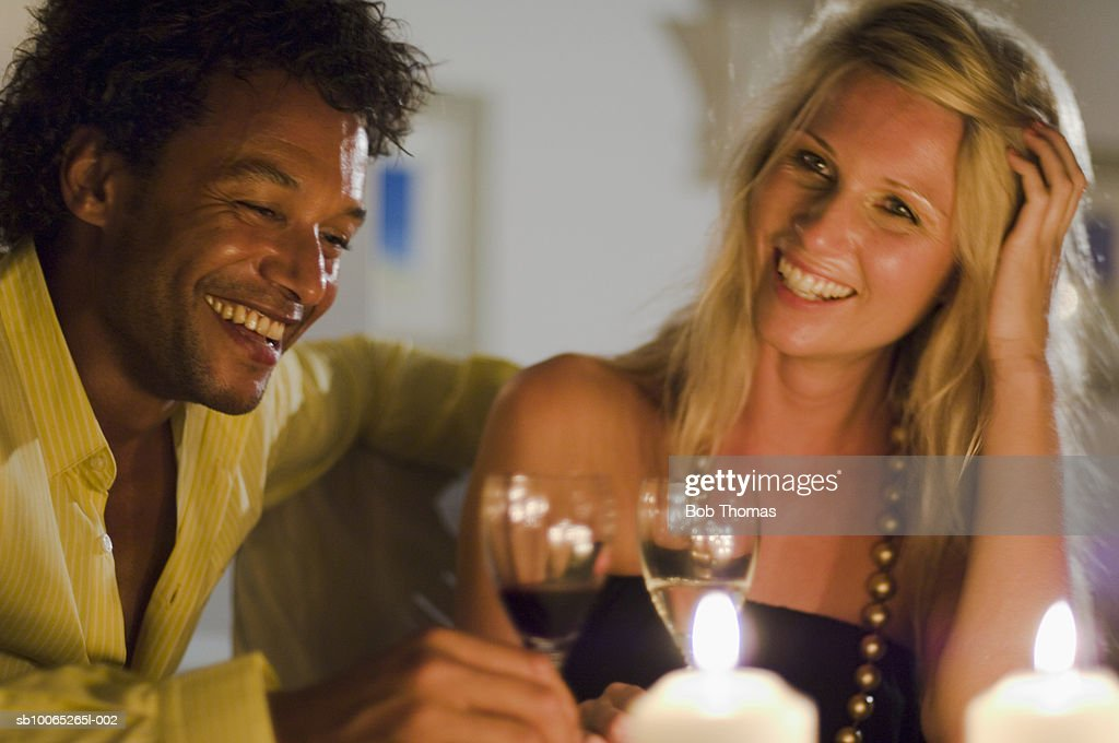 Couple at candlelit dinner holding wine glass, smiling : Foto stock