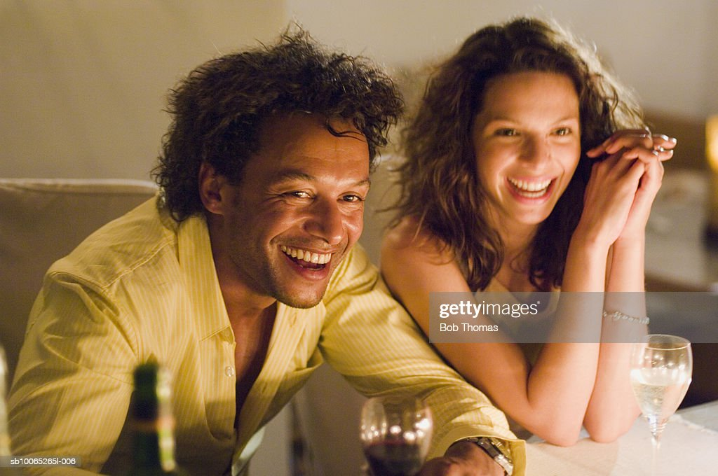 Couple at candlelit dinner, looking away, laughing : Foto stock