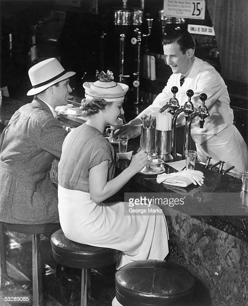 couple at counter of ice cream parlor - ice cream parlor stock photos and pictures