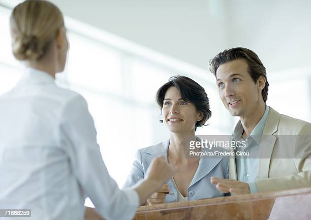 Couple at counter speaking to receptionist