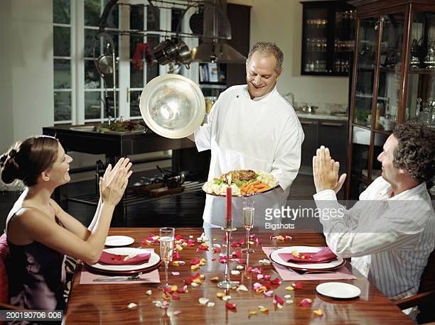 Couple at dinner table applauding chef holding dish of food