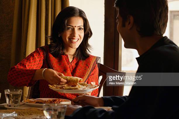 couple at dinner table, woman offering food
