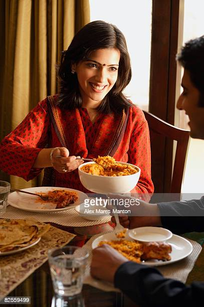 couple at dinner table, woman serving food