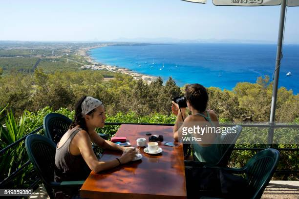 Couple at Es Mirador bar and restaurant Ibiza and Es Vedra rock at the sunset FORMENTERA Balearic Islands SPAIN