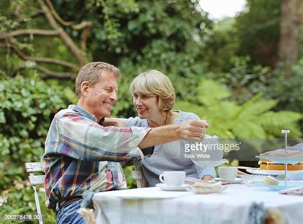 Couple at garden table, man pouring tea