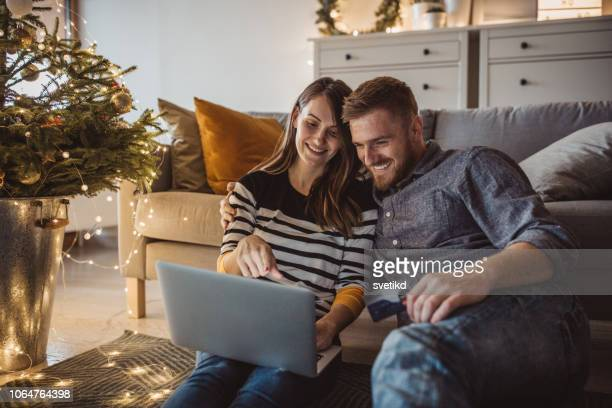 couple at home for christmas - christmas shopping stock photos and pictures