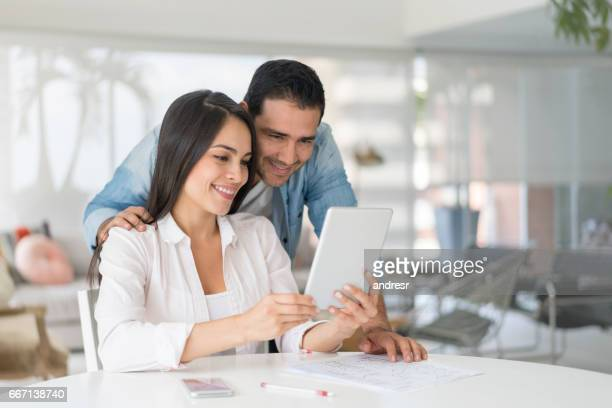 Couple at home looking at a tablet computer