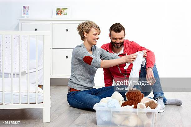 Paar zu Hause Blick auf Kleidung für Babys