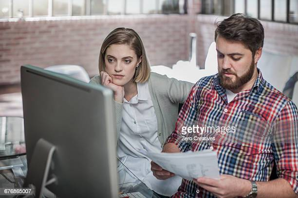 Couple at home, looking at computer screen, man holding paperwork