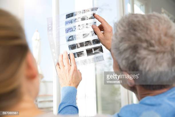 Couple at home looking at old photographies