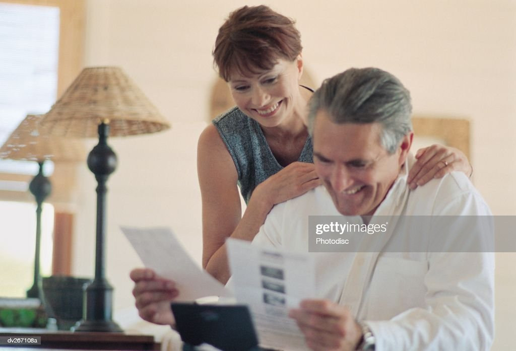 Couple at home looking at paperwork : Stock Photo