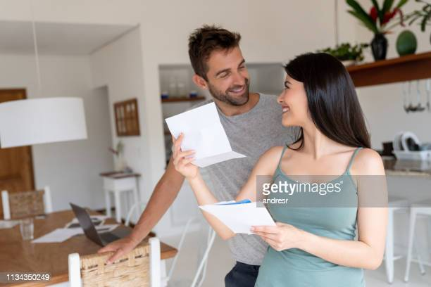 pares em casa que olham felizes verific seu correio - responder - fotografias e filmes do acervo