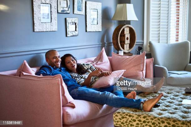 couple at home watching television together on sofa - sunday stock pictures, royalty-free photos & images