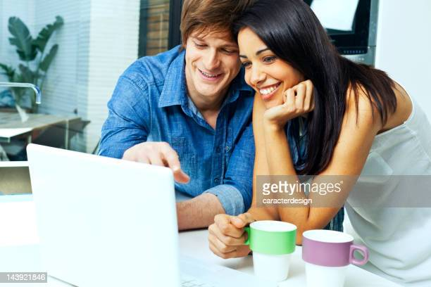 Couple at home with laptop.