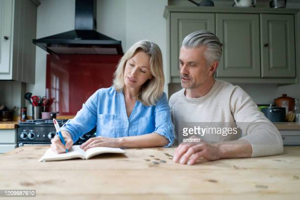 couple at home writing down the budget for their home finances - currency stock pictures, royalty-free photos & images