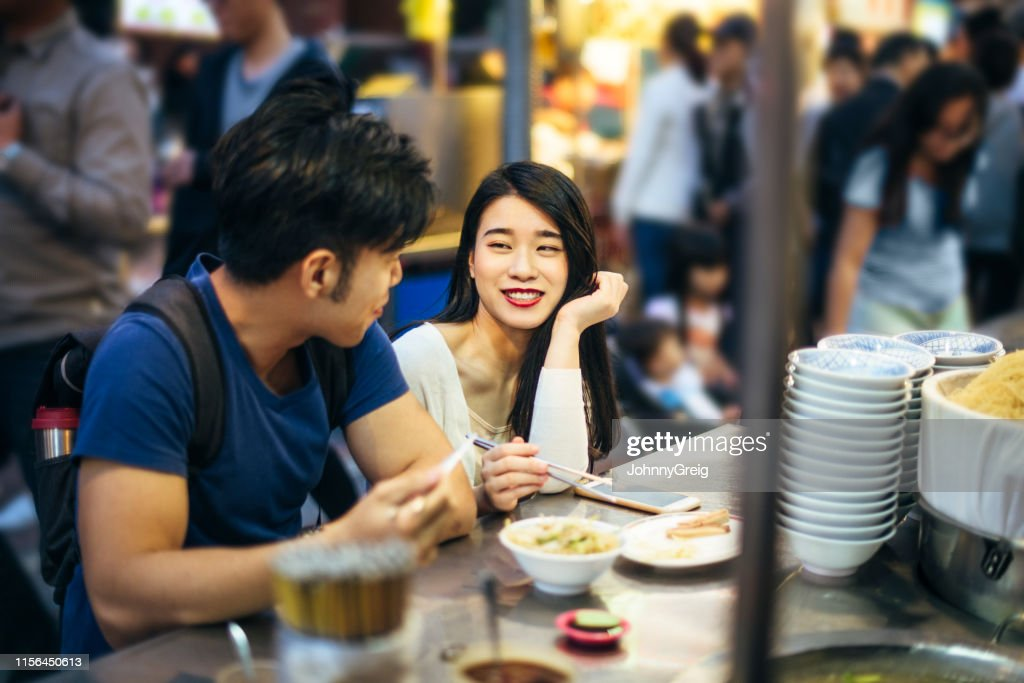 Couple at night market stall eating noodles : Stock Photo