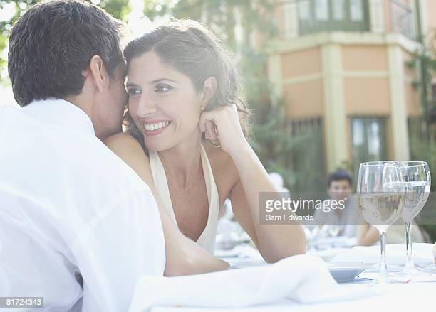 couple at outdoor party whispering and smiling - may december romance stock photos and pictures
