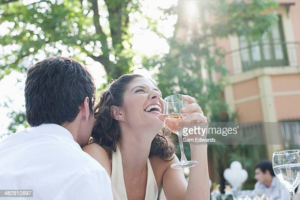 Couple at outdoor party with white wine laughing