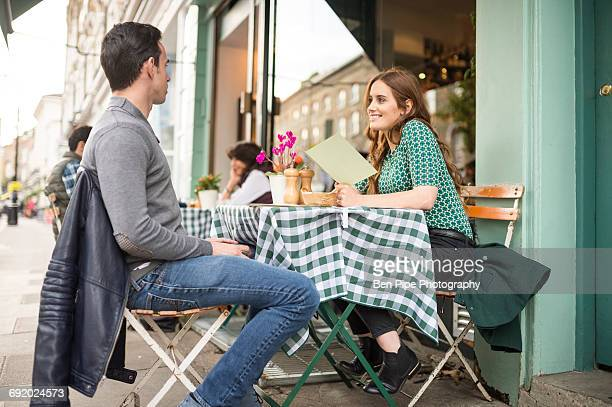 Couple at pavement cafe looking at menu smiling