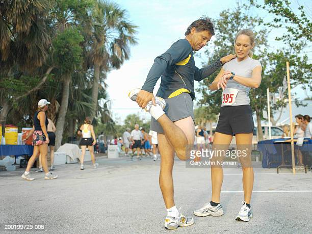 Couple at race, man stretching leg, woman checking watch