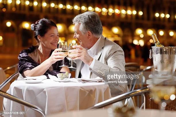 Couple at restaurant in square, toasting drinks, smiling, night