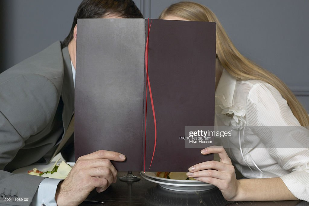 Couple at restaurant table leaning towards each other behind menu : Stockfoto