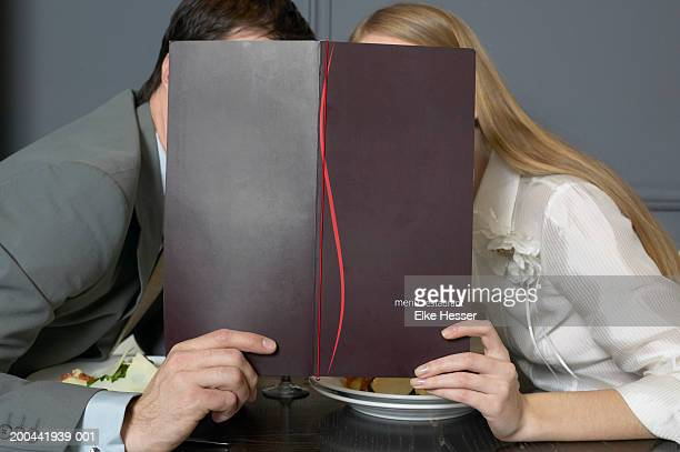 Couple at restaurant table leaning towards each other behind menu