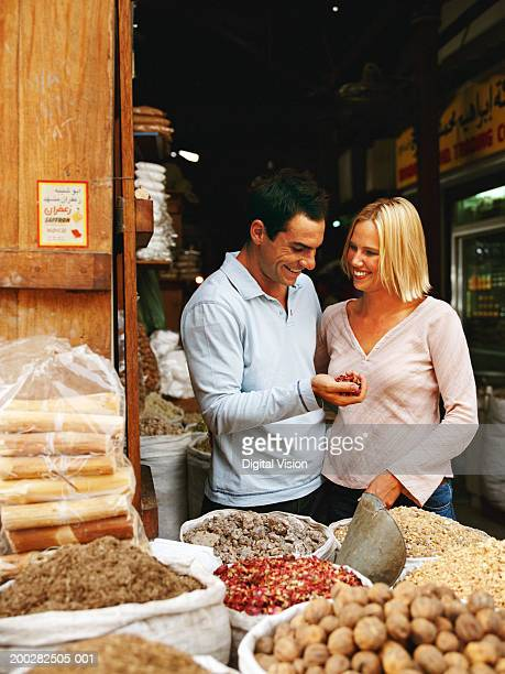 Couple at spice store, man with handful of dried chillis, smiling