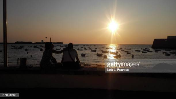Couple at sunset in Caleta beach, Cadiz r
