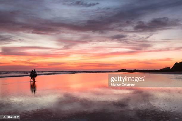 couple at sunset walking on beach, playa guiones, costa rica - península de nicoya fotografías e imágenes de stock