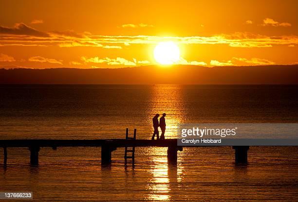 Couple at sunset walking on pier
