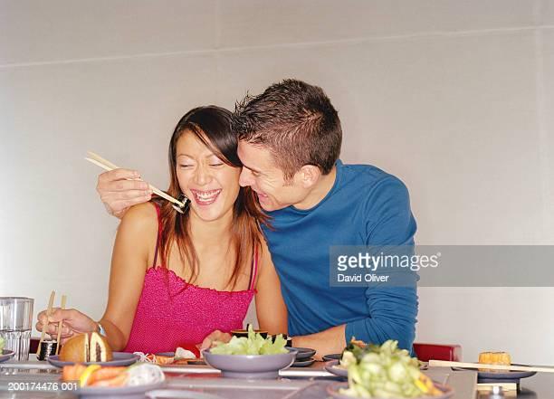 Couple at sushi bar, man feeding woman