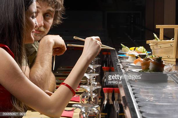 couple at sushi bar - sushi restaurant stock photos and pictures