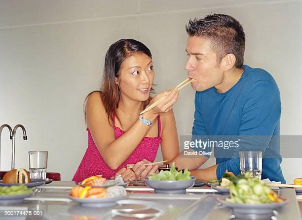 Couple at sushi bar, woman feeding man