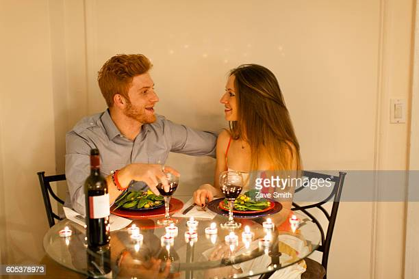 Couple at table face to face enjoying candlelit meal, smiling