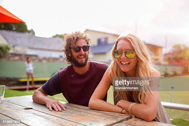 Couple at table laughing at lawn bowls club Australia