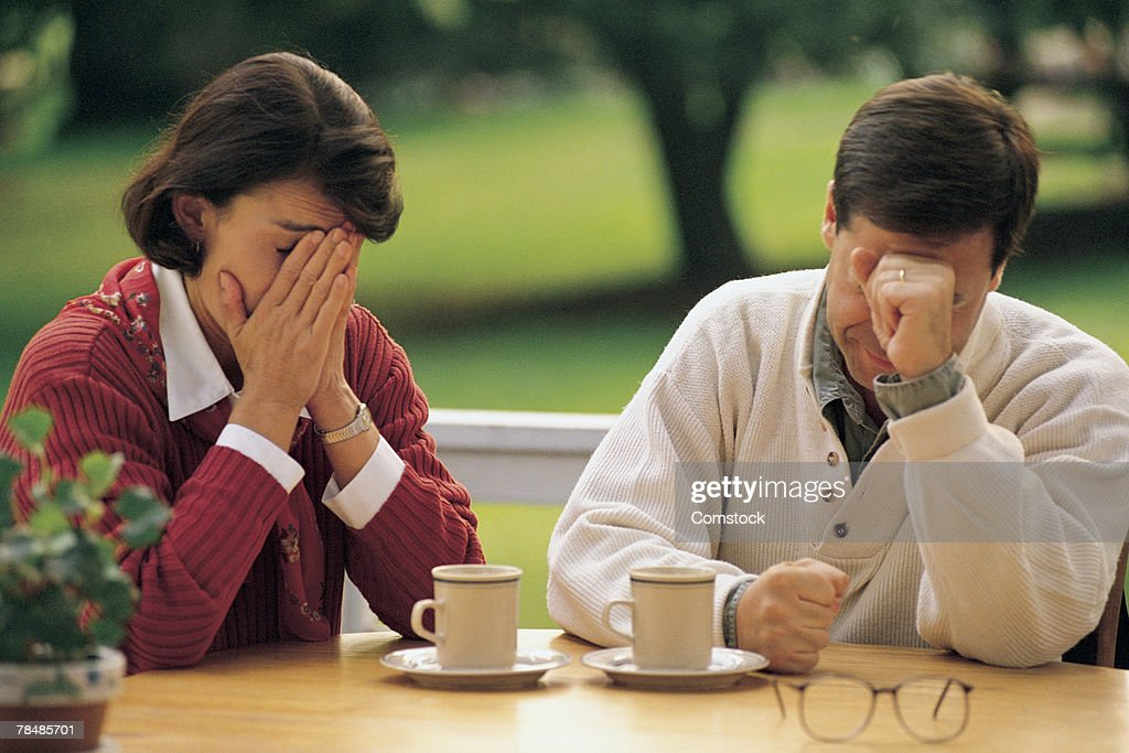 Couple at table looking upset : Stock Photo