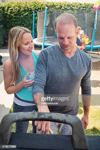 Paar im barbecue, während Ihre Kinder auf Trampolin im Hintergrund.