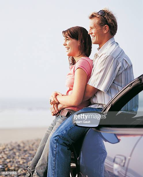 couple at the beach looking at the view standing next to their car - next to stock pictures, royalty-free photos & images