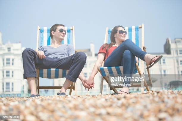 Couple at the beach sitting in deckchairs, holding hands