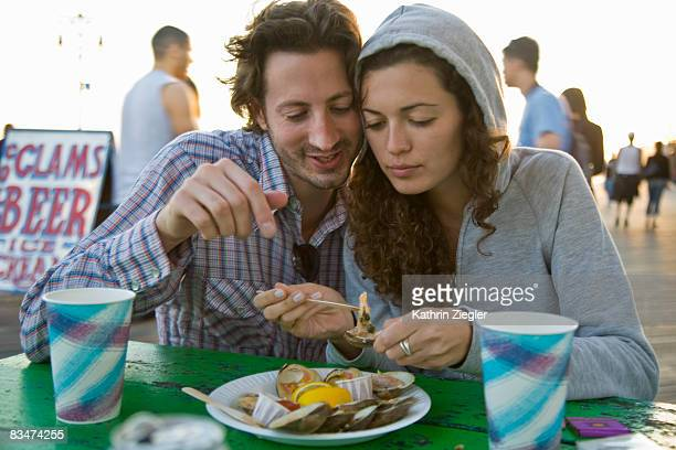 couple at the boardwalk, eating clams