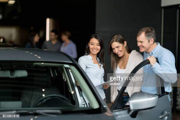 couple at the dealership buying a car and talking to a saleswoman - test drive stock pictures, royalty-free photos & images